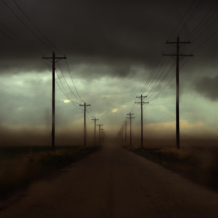 A photograph looking down a road lined with electricity poles - the air is coloured grey and yellow by particles in the air.