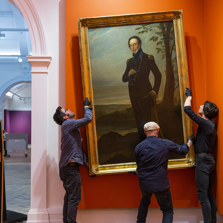 Three intallers handle a large guilt-framed oil painting of a man in military uniform, onto the wall of a gallery.