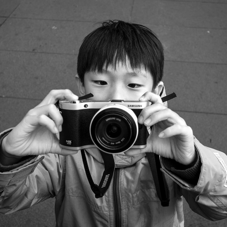 A black and white photo of a small boy holding a camera up in front of his face to take a photo - he is standing on concrete paving and wearing up a zip up parka.