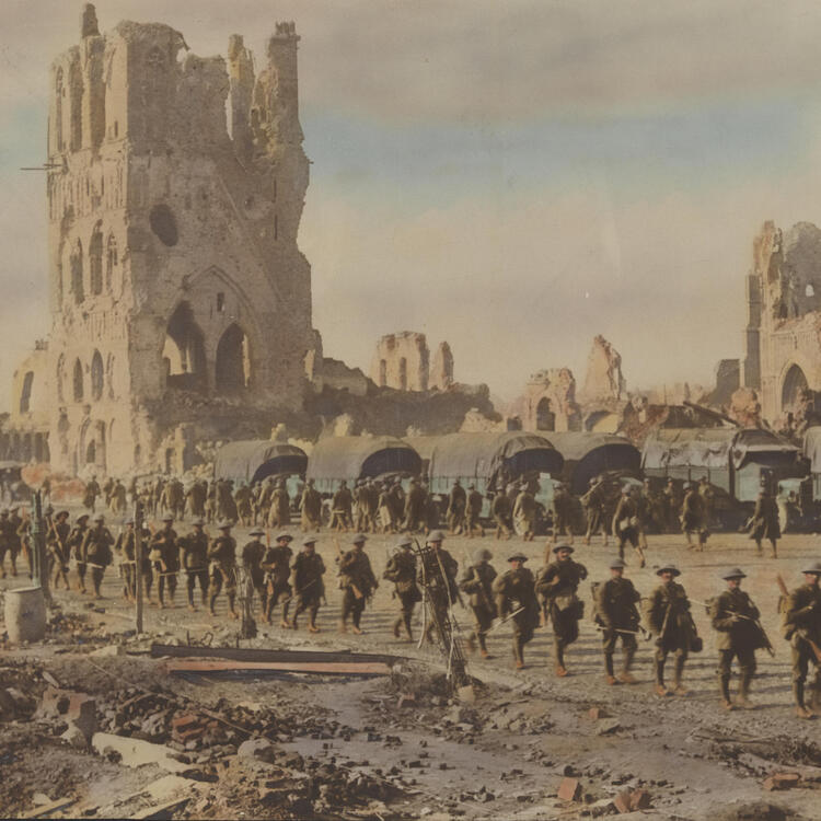 A hand coloured photograph of soldiers filing past the ruins of grand buildings.