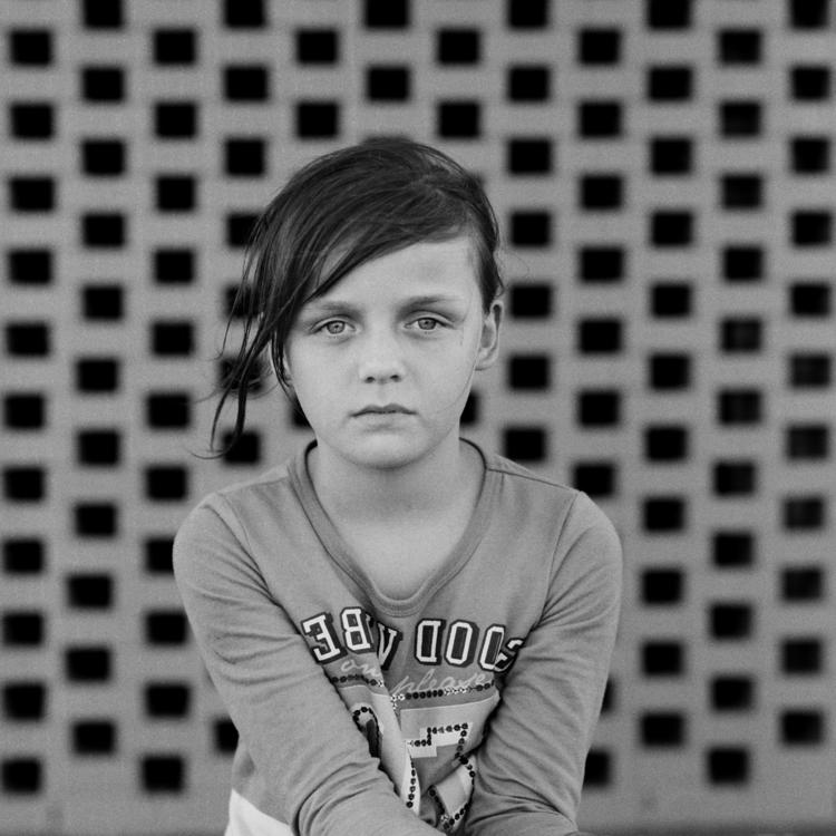 A black and white photograph of a young girl sitting with her leg crossed, holding a camera release cable.