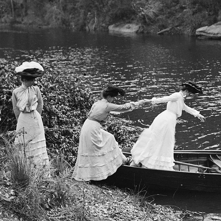 Black and while photograph of women in 19th century dress helping one another into a row boat at the shore of a river.