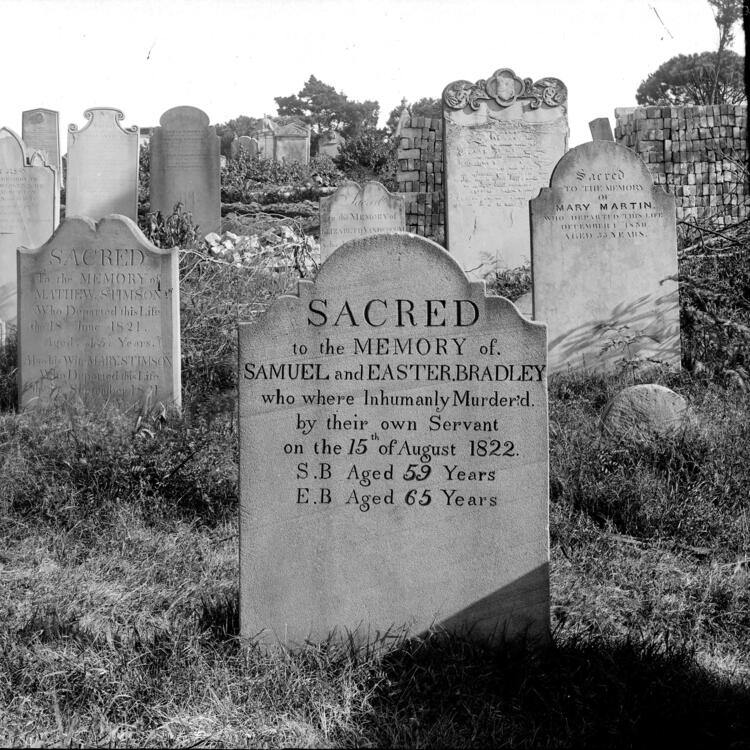 Black and white photograph of gravestones in a cemetery.