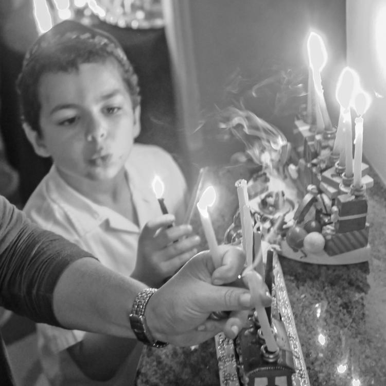 A black and white photograph of a woman lighting the candles for Hanukkah with her daughter and son.