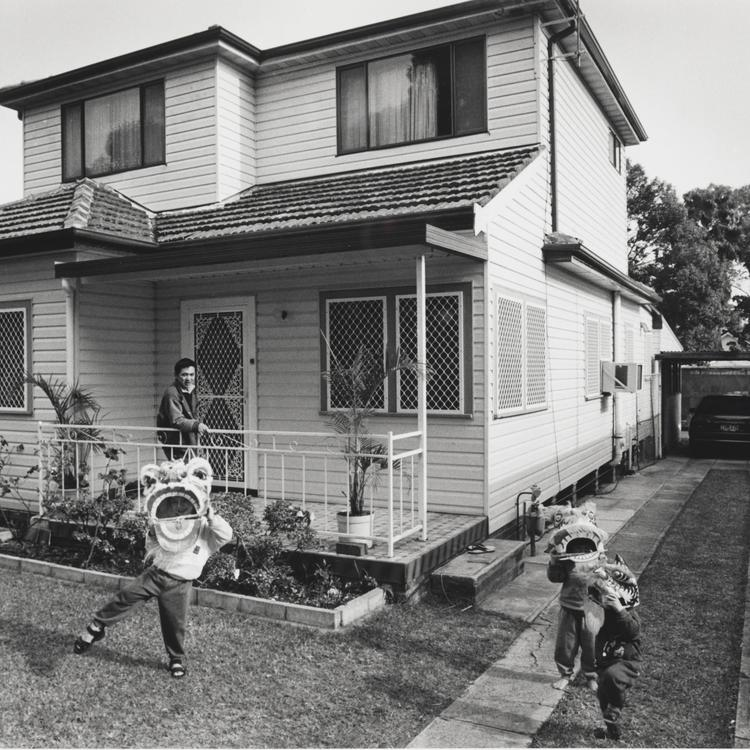 Three children wearing Chinese dragon paper heads play in a suburban front yard, their father watching on from the front verandah.