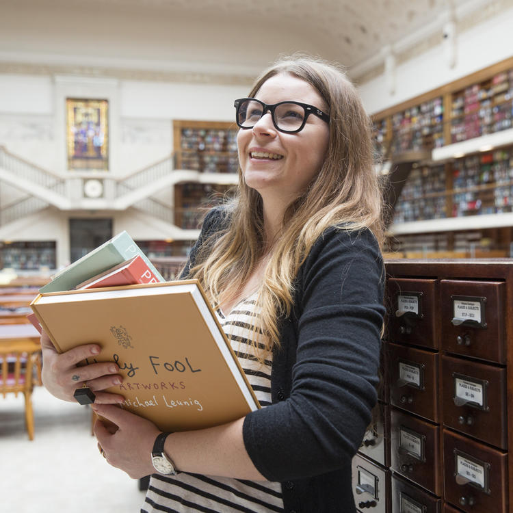 Women browsing shelves while holding books in the Mitchell Library Reading Room