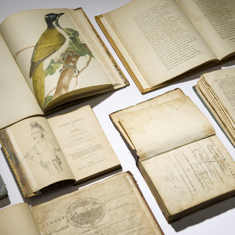 Several rare books open at pages displaying text and drawings