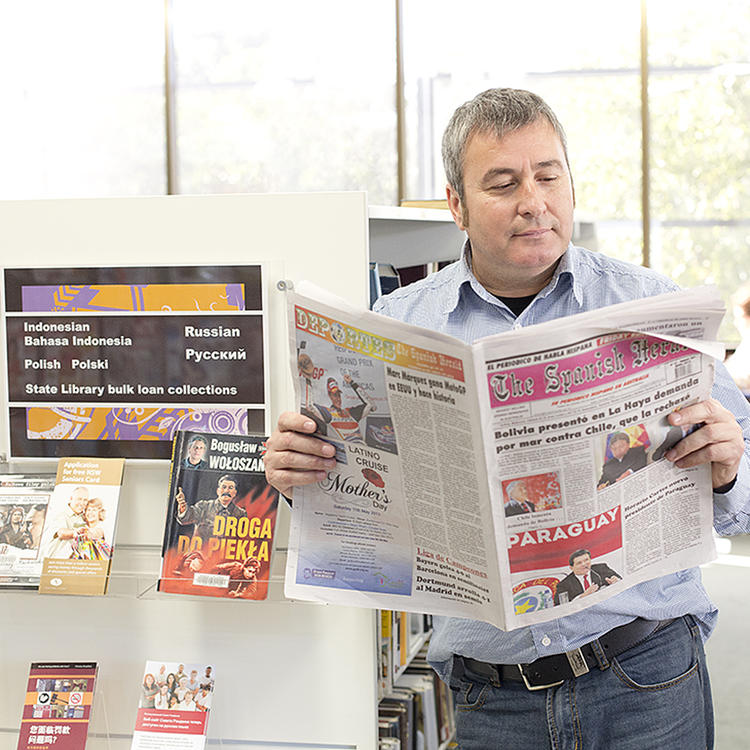 Client reading Spanish newspaper in reading room