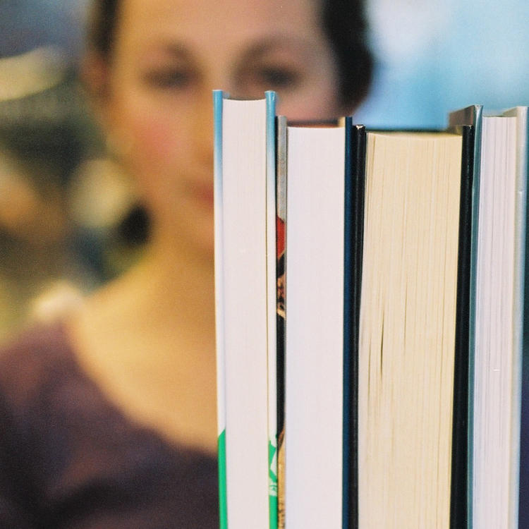 Woman standing behind row of books