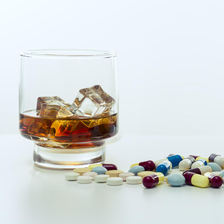 Scattered pills sitting next to glass of alcohol