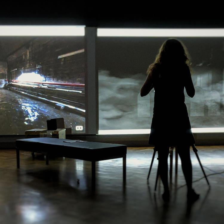 A woman standing in front of two projector screens showing pipelines and gravestones.