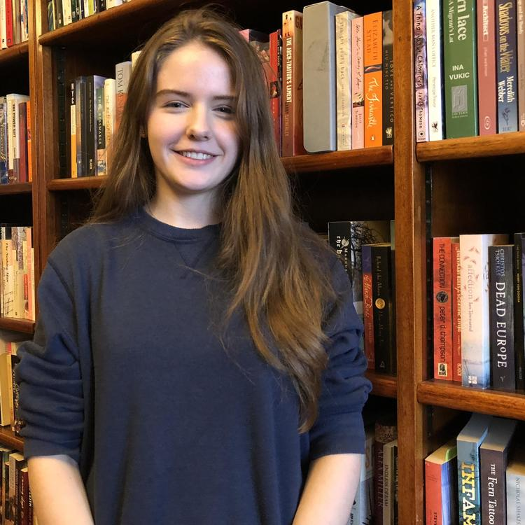 A HSC student standing in front of a bookcase