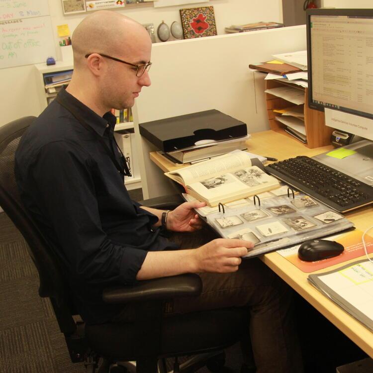 A man looking at a printed book