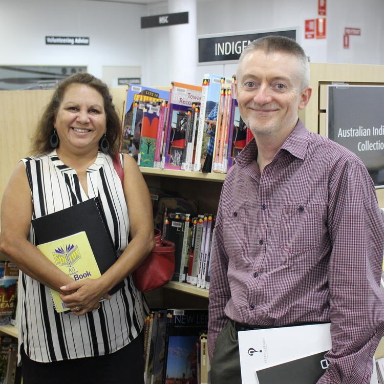 2 people in front of books