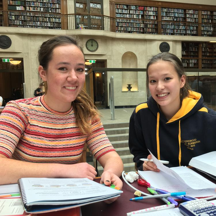 Two girls in the Mitchell Library reading room studying