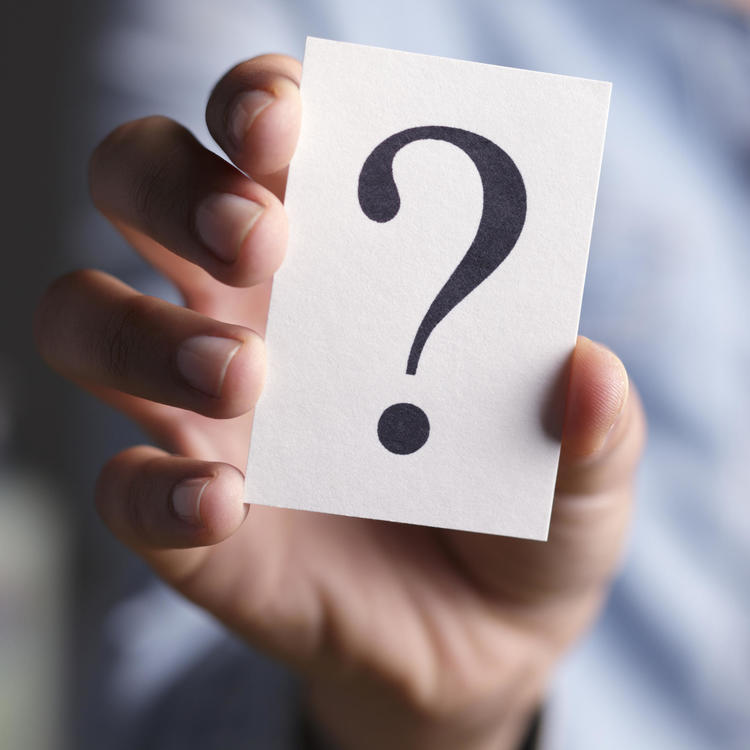 Hand holding piece of paper with question mark printed on it
