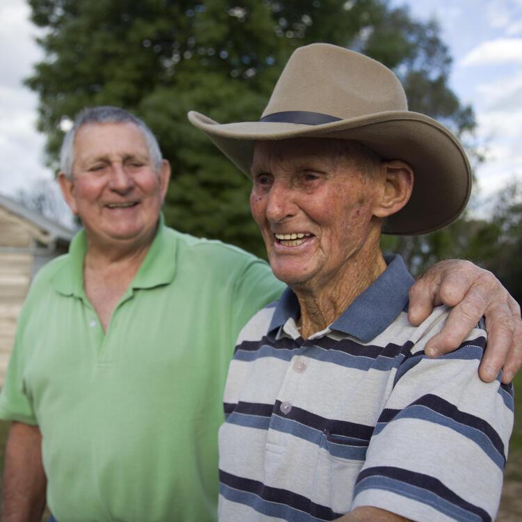 Man with arm around older man wearing a hat