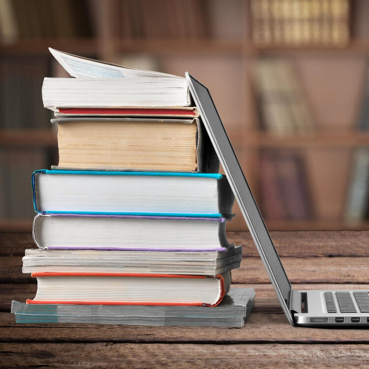 Laptop leaning next to a stack of books