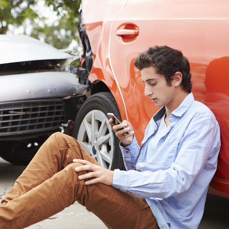 Young man leaning against damaged car after accident
