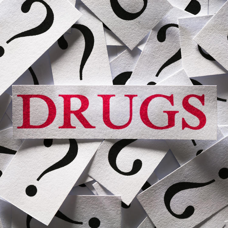 Pile of cards with question marks on them and the word drugs in the middle