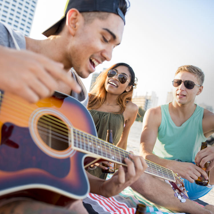 Group of youth on the beach with a guitar