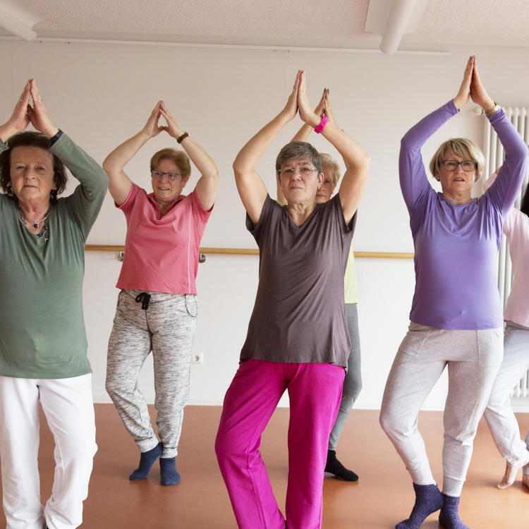 Group of middle aged women practising yoga