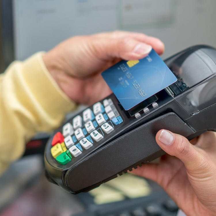 hand tapping a credit card on an eftpos machine