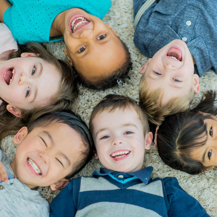 Group of pre-school children lying in a circle on the floor