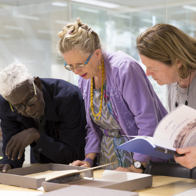 two women and a man looking at a photograph on a white table