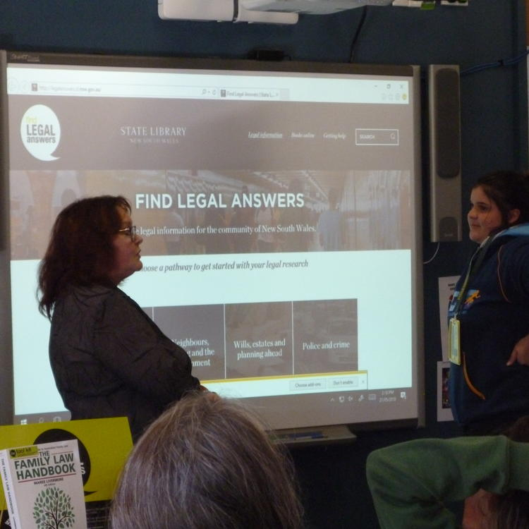 Woman and young woman standing in front of a screen displaying the Find Legal Answers website