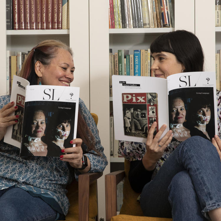 Two women holding up the winter edition of SL Magazine