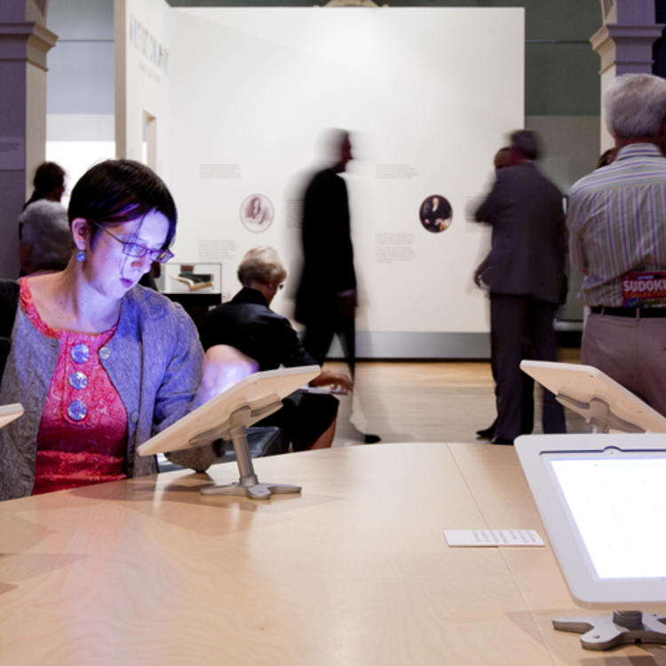 Two women looking at tablet displays in a gallery