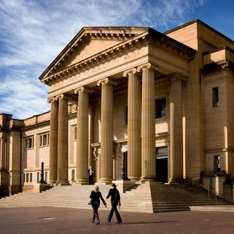 Large sandstone building with blue sky behind and people walking to it