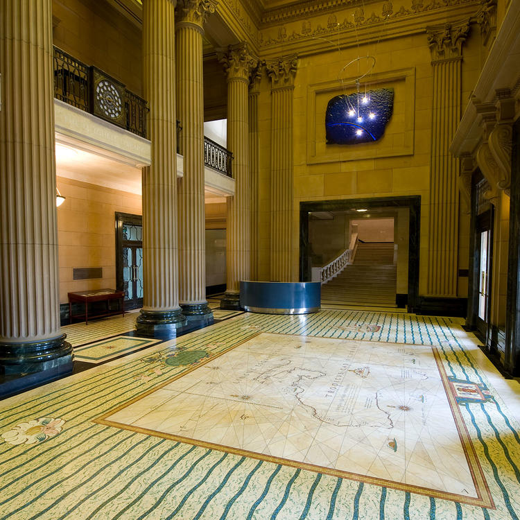 The Mitchell building foyer. With a lofty ceiling, there are grand columns, and the marble floor depicts a map.