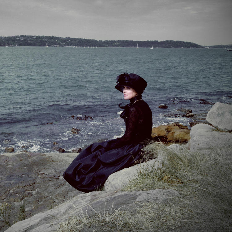 A woman sitting by the sea.
