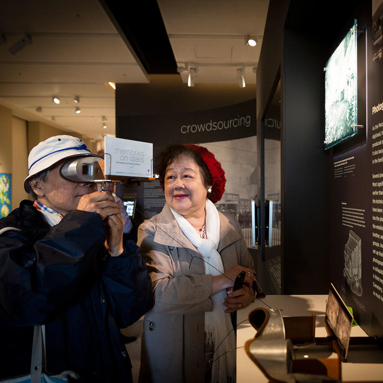 """In front of an exhibition display, a man looks through a viewing device to a slide titled """"Memories on glass"""". A woman wearing a red hat is standing next to him, smiling at him."""