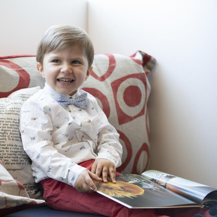 small boy in a bow tie reading a book