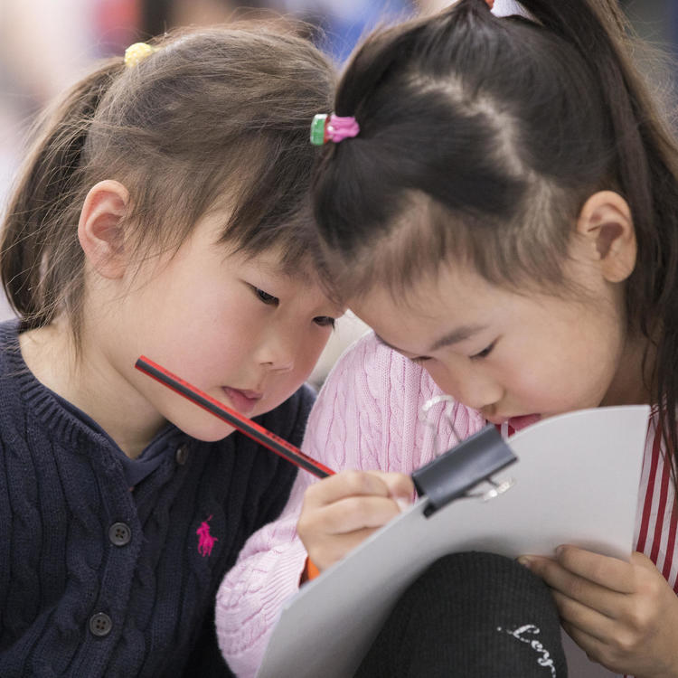 Two girls drawing on paper