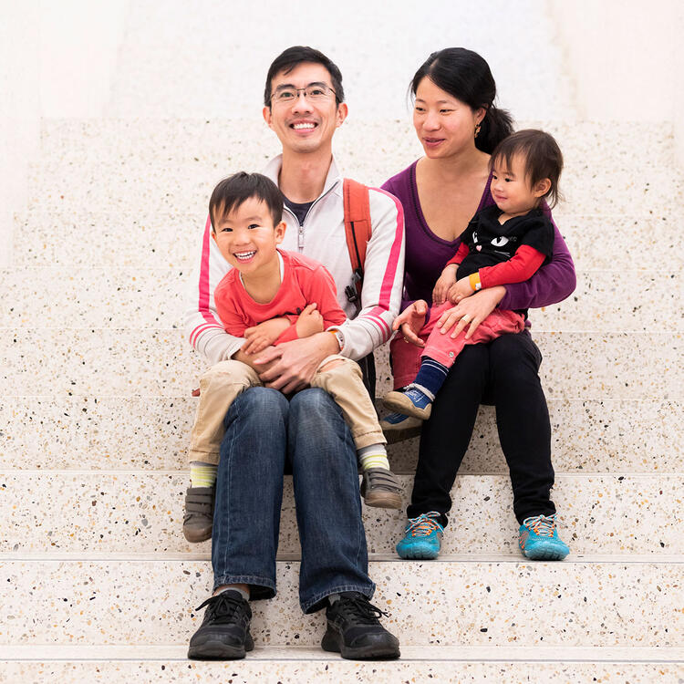 A family sits on marble steps.