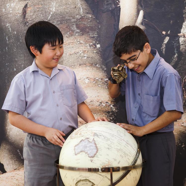 Two school boys with world globe