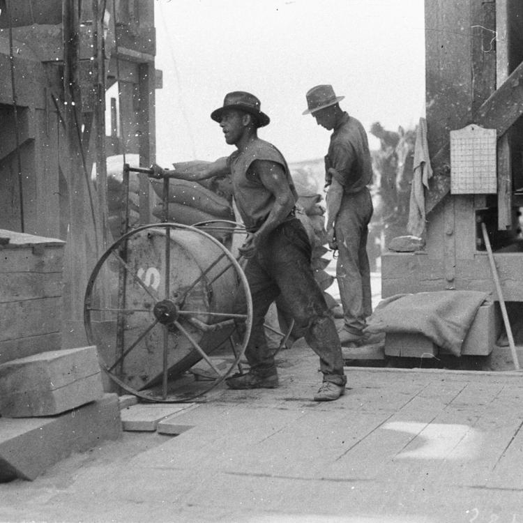 Workmen mixing and pouring concrete with small hand-wheeled hoppers Creator Hood, Ted, 1911-2000, Call Number, Home and Away - 2262 Digital Order No. hood_02262