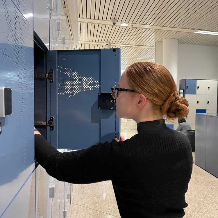 Woman with her back to the camera putting her belongings into a Library locker.