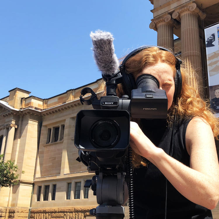 Camera person in front of the Mitchell Library
