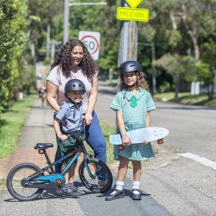 A woman standing on a footpath with two children, a young boy holding a bike and a girl holding a skateboard