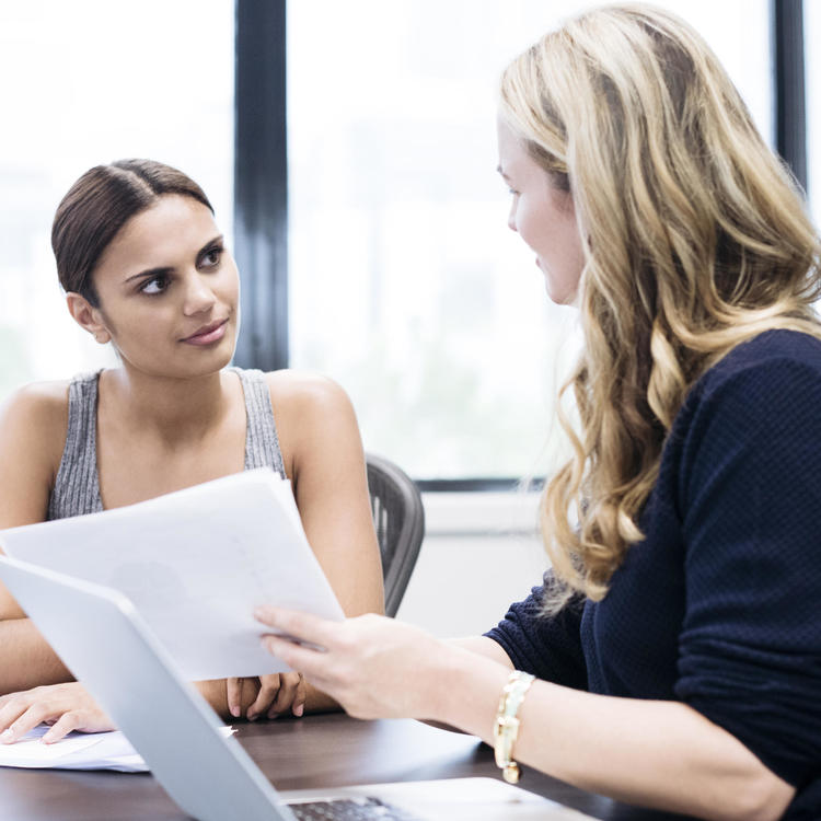 Two women speaking in office with paperwork