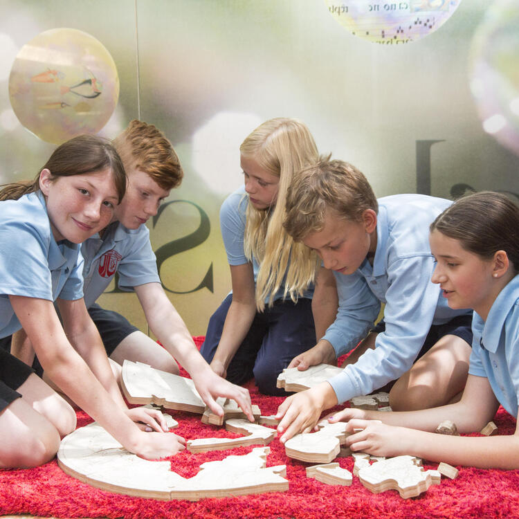 three girls and two boys sitting on red mat completing puzzle