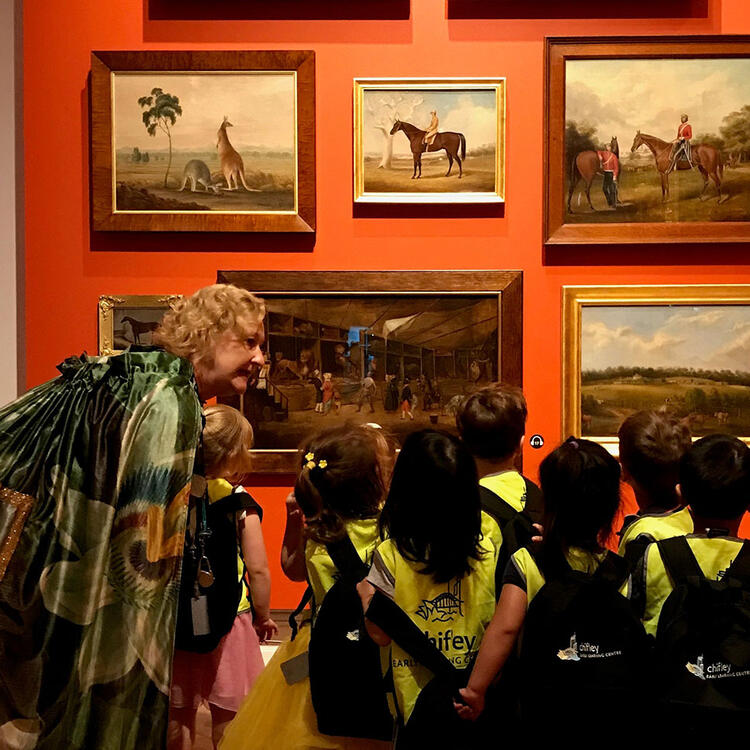A woman leads a group of young children around a painting gallery.