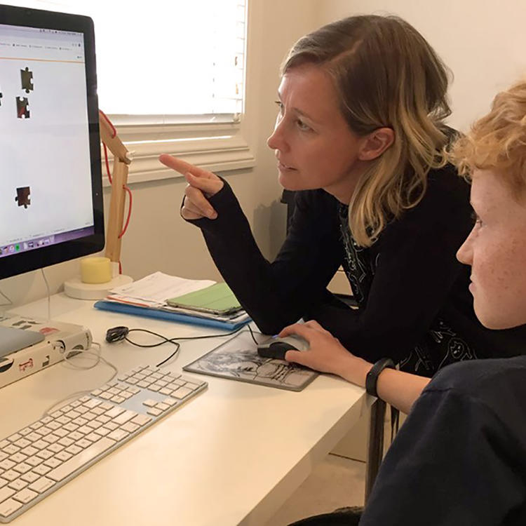 A parent and child, looking at a puzzle on a computer screen
