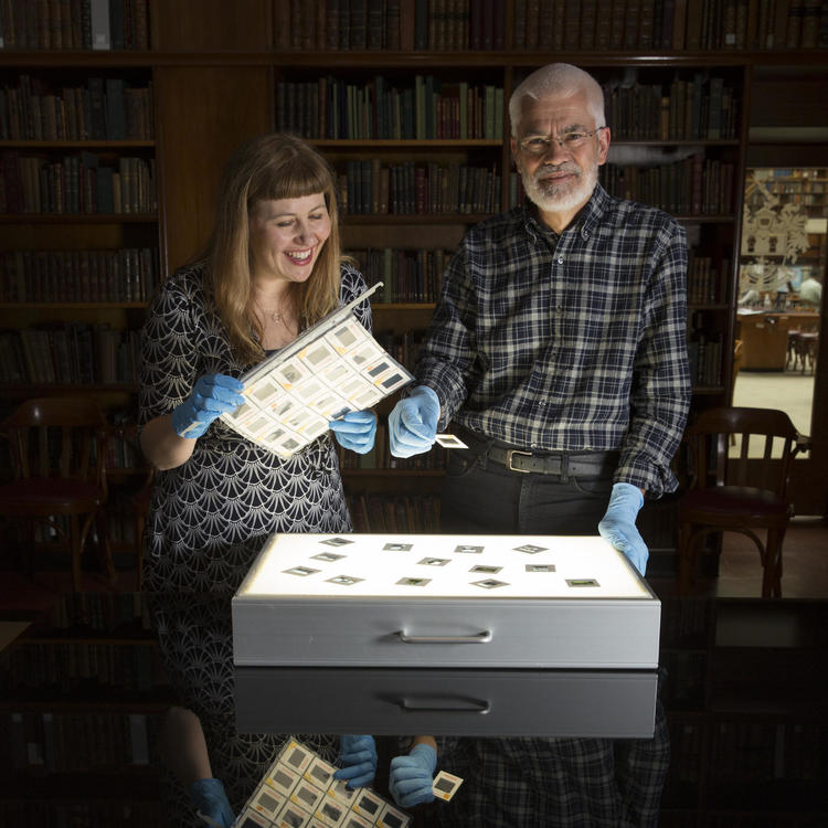 A man and woman, wearing gloves, stand in front of a light box looking at slides.