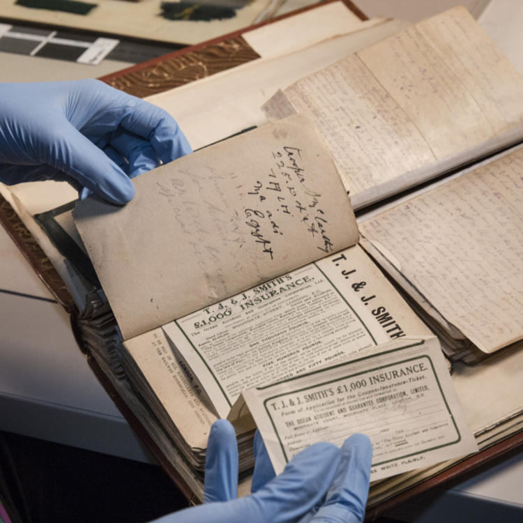 Gloved hands handling leather diaries and newspaper cuttings